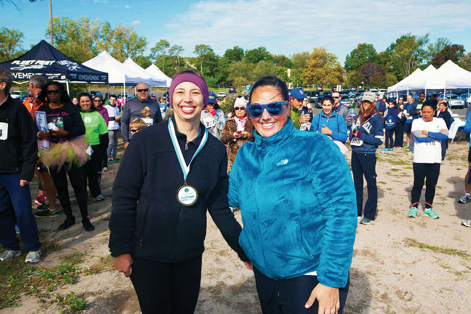 Emily Walgenbach of Stamford (left) CancerCare's Walk/Run for Hope Women's 5K winner, with Corey Cenatiempo, regional special events manager for CancerCare, at Jennings Beach in Fairfield on Sunday, Oct. 4.