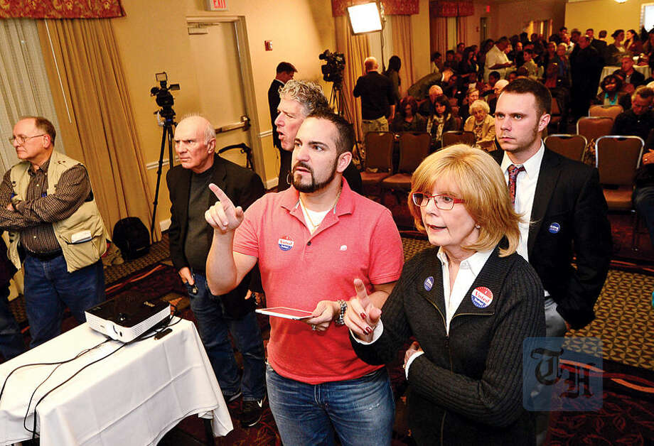 Hour photo / Erik Trautmann Democrats check election results at the Hilton Garden Inn Tuesday night in Norwalk.