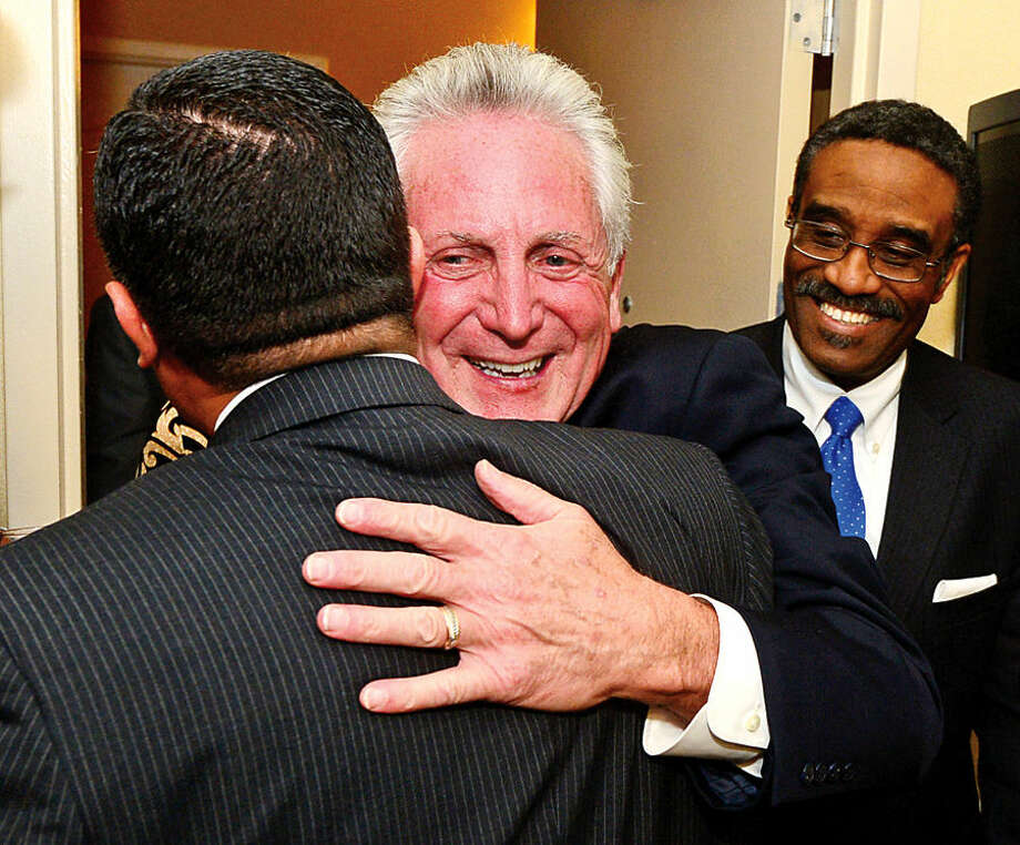 Hour photo / Erik Trautmann Warren Pena congratulates Norwalk Hayor Harry Rilling as he celebrates his reelection with other democrats including State Representatives Bruce Morris aat the Hilton Garden Inn Tuesday night.