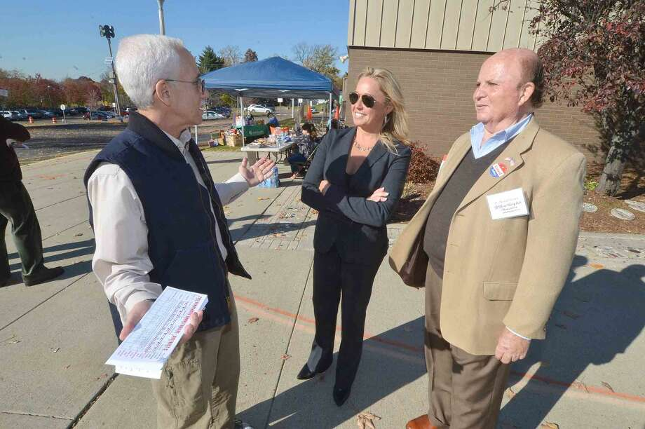 Hour Photo/Alex von Kleydorff Bruce Kimmel Councilman at Large, Michelle Maggio Councilwoman and Michael Intrieri forThird Taxing District Treasurer, talk with voters in front of Marvin Elementary School on Election day