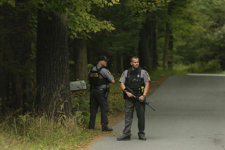 Pennsylvania State Troopers walk along a wooded area on Bear Town Road near Route 447 in Barrett Township on Saturday, Sept. 20, 2014, near Canadensis, Pa., during a search for suspected killer Eric Frein. Frein is suspected of fatally shooting a state trooper and wounding another at the Blooming Grove state police barracks a week earlier. (AP Photo/Scranton Times & Tribune, Butch Comegys)