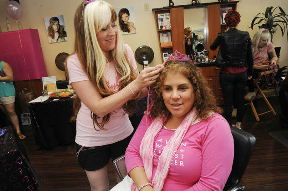 Emilie Forcellina, owner of Stylin' salon in Norwalk puts pink extensions in the hair of Audra Good who has been involved in the Avon Breast Cancer Walk every year since it began. Stylin' salon is helping Audra raise money for the event. Hour photo/Matthew Vinci