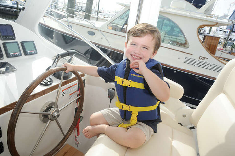 Trevor Bobbin 3, gets a chance to steer a boat Sunday at the Norwalk Boat Show at Norwalk Cove Marina. Hour photo/Matthew Vinci
