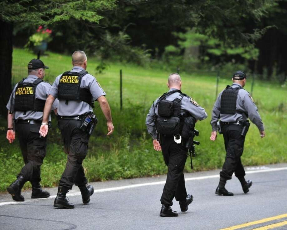 Police surround a neighborhood in the Pocono Mountains in search of suspect Eric Frein on Saturday, Sept. 20, 2014 in Canandensis, Pa. Police have charged Frein with opening fire outside a state police barracks in northeastern Pennsylvania on Sept. 12. Cpl. Bryon Dickson was killed and Trooper Alex Douglass was wounded by the gunman with a high-powered rifle. (AP Photo/Chris Post)