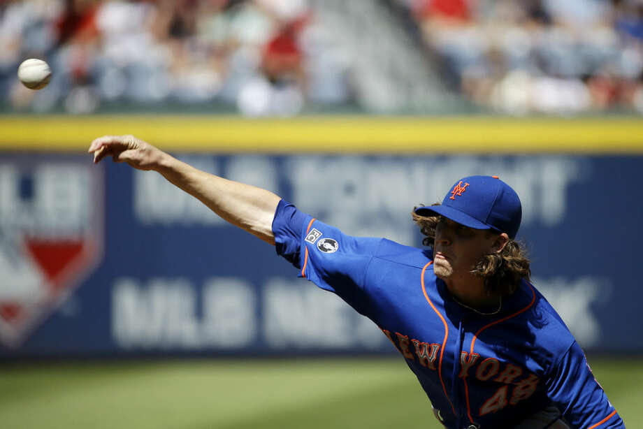 New York Mets starting pitcher Jacob deGrom throws in the first inning of a baseball game against the Atlanta Braves, Sunday, Sept. 21, 2014, in Atlanta. (AP Photo/David Goldman)