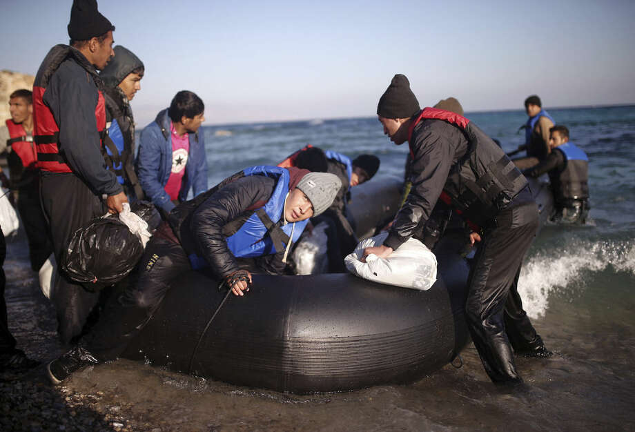 Migrants board a dinghy to travel to the Greek island of Chios, from the Turkish coast near Cesme, Izmir, Turkey, Wednesday, Nov. 4, 2015. More than 300,000 people have traveled on dinghies and boats from nearby Turkey to Greek islands this year, with dozens dying along the way.(AP Photo/Emre Tazegul)