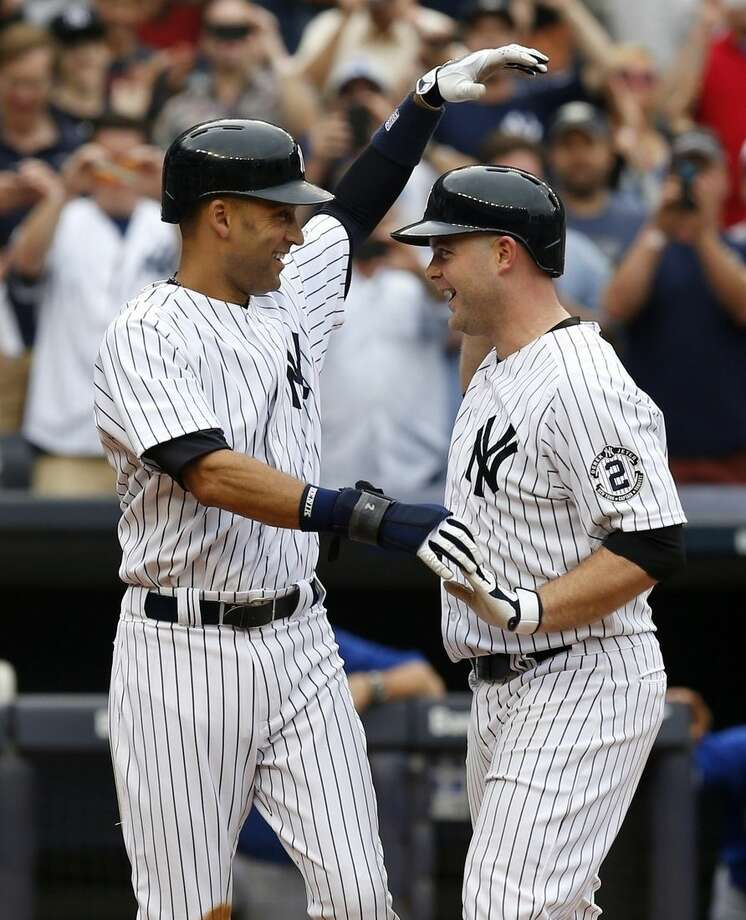 New York Yankees' Derek Jeter, left, greets Brian McCann after McCann hit a two-run homer during the seventh inning of the baseball game against the Toronto Blue Jays at Yankee Stadium, Sunday, Sept. 21, 2014 in New York. (AP Photo/Seth Wenig)