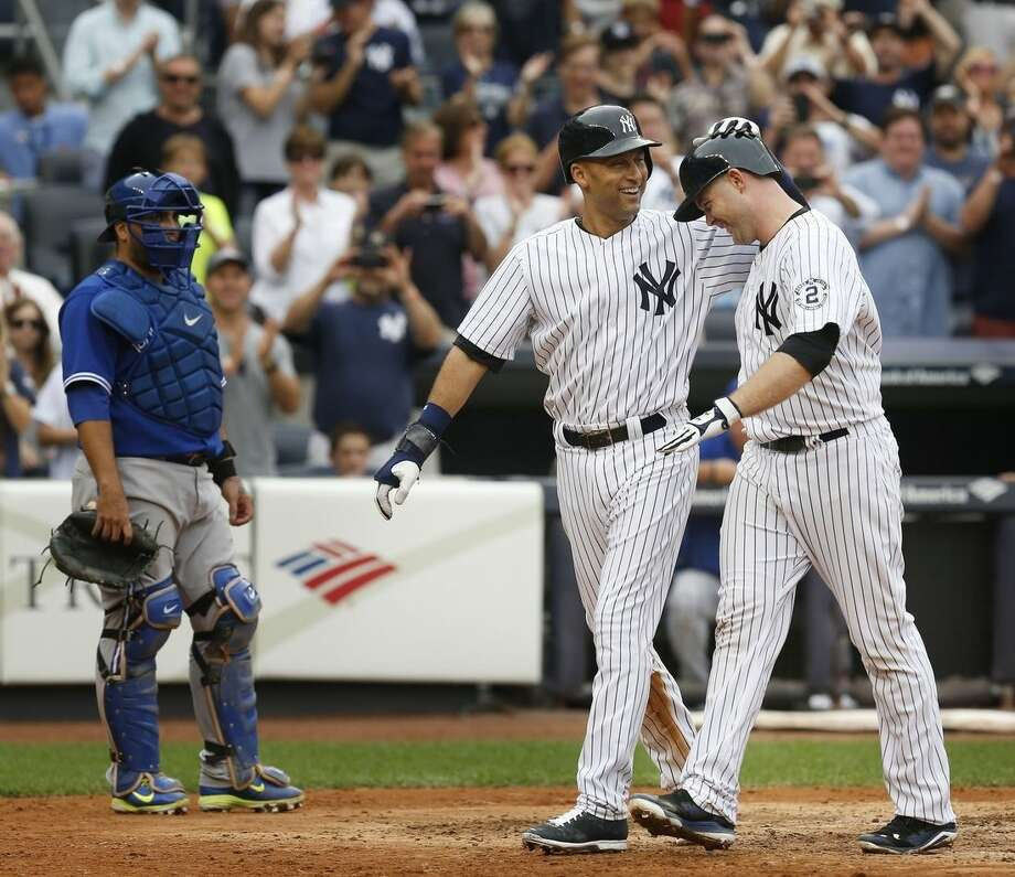 While Toronto Blue Jays catcher Dioner Navarro, left, looks on, New York Yankees' Derek Jeter, center, celebrates with Brian McCann after McCann hit a two-run homer during the seventh inning of the baseball game at Yankee Stadium, Sunday, Sept. 21, 2014 in New York. (AP Photo/Seth Wenig)