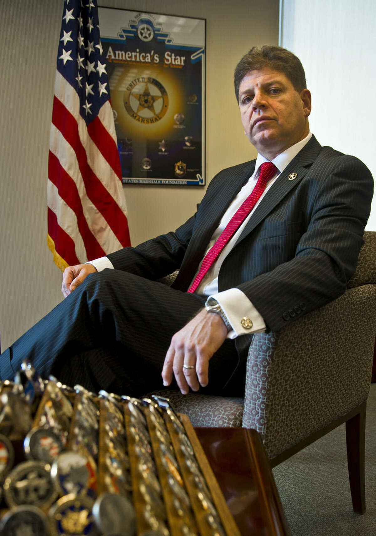 """U.S. Marshall Director Michael Greco pose in his office next to his collection of """"Challenge Coins"""" in the foreground, representing military and law enforcement institutions, Thursday, Oct. 8, 2015, in New York. (AP Photo/Bebeto Matthews)"""