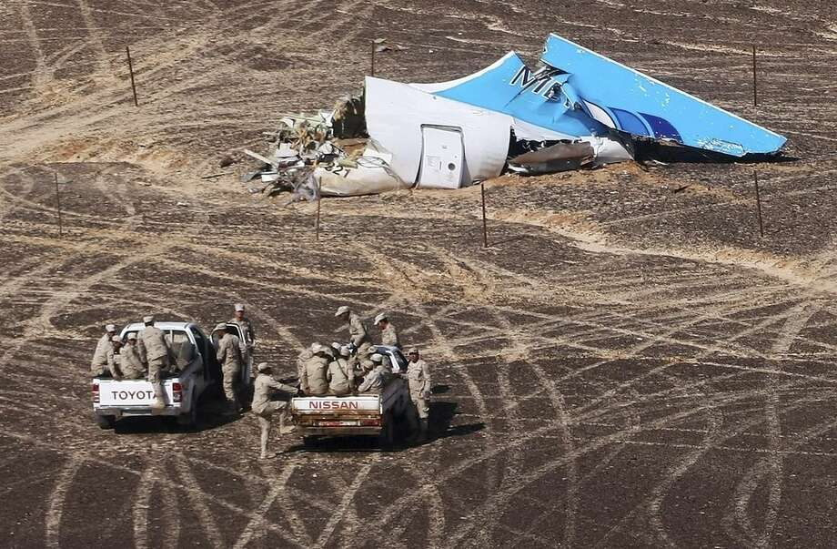 In this photo made available Monday, Nov. 2, 2015, and provided by Russian Emergency Situations Ministry, Egyptian Military on cars approach a plane's tail at the wreckage of a passenger jet bound for St. Petersburg in Russia that crashed in Hassana, Egypt, on Sunday, Nov. 1, 2015. The Russian cargo plane on Monday brought the first bodies of Russian victims killed in a plane crash in Egypt home to St. Petersburg, a city awash in grief for its missing residents. (Maxim Grigoriev/Russian Ministry for Emergency Situations via AP)