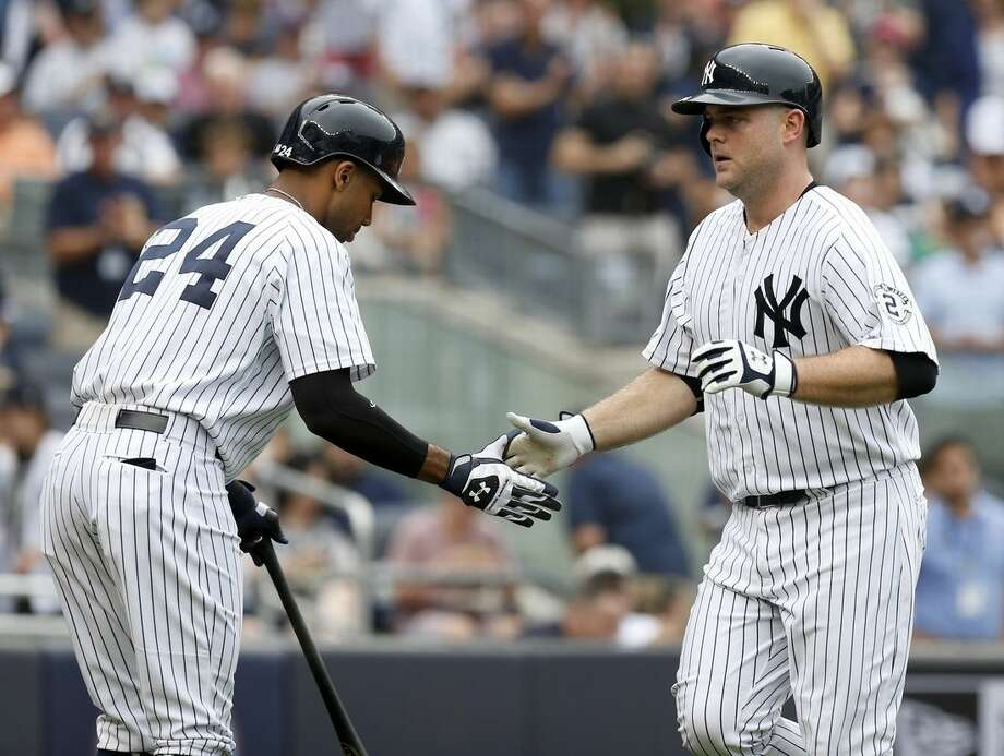 New York Yankees' Brian McCann, right, celebrates his solo home run with Chris Young during the first inning of the baseball game against the Toronto Blue Jays at Yankee Stadium, Sunday, Sept. 21, 2014 in New York. (AP Photo/Seth Wenig)
