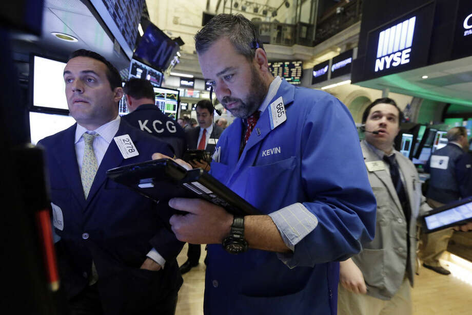 Trader Kevin Lodewick, center, works on the floor of the New York Stock Exchange, Monday, Nov. 2, 2015. Stocks opened slightly higher on Wall Street as the market comes off its biggest monthly gain in four years. Health care stocks were among the early winners. (AP Photo/Richard Drew)