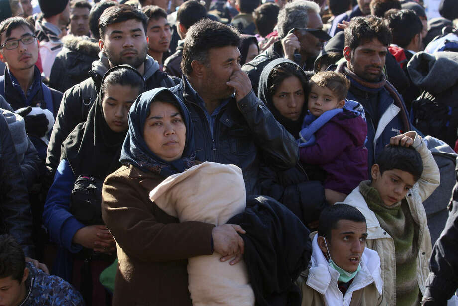 Migrants wait to cross the border between Slovenia and Austria in Sentilj, Slovenia, Wednesday, Nov. 4, 2015. Hundreds of thousands of migrants have flooded to northern Europe in recent months seeking to escape war and poverty and start a new life. (AP Photo/Ronald Zak)