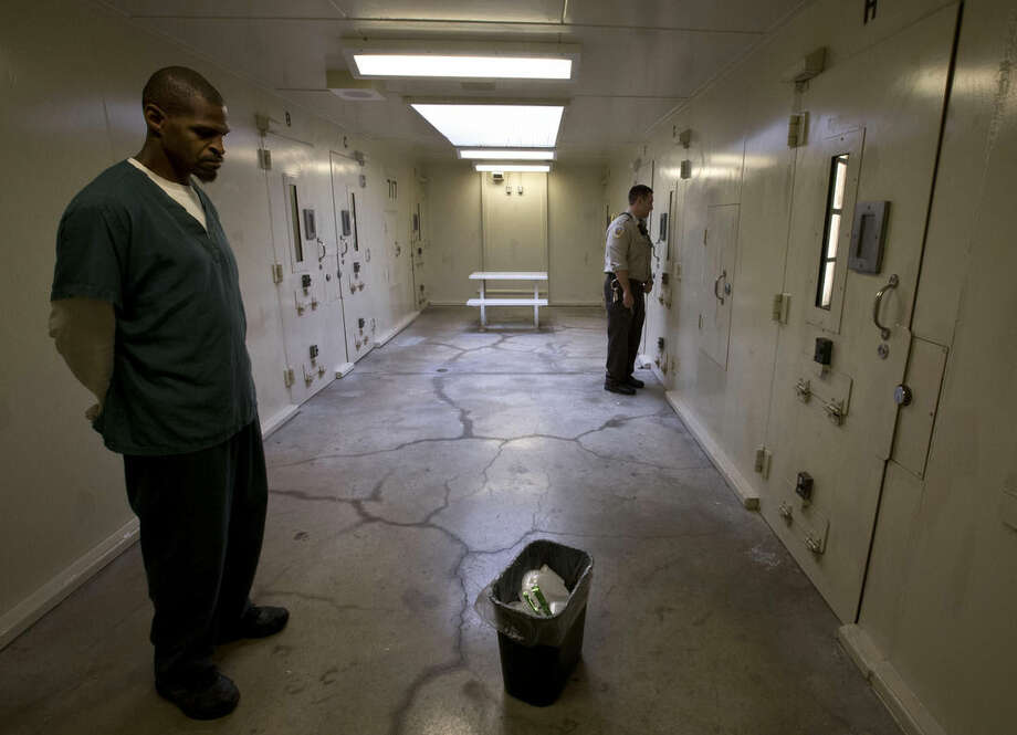 In this Sept. 16, 2014, photo, inmate worker James Tate, left, waits as deputy Matt Matteson talks to an inmate through the door of an isolation cell in the Dane County Jail in Madison, Wis. Jails use isolation to punish inmates, but it also is frequently used to separate those with serious mental illnesses because officials worry they may be victimized by fellow inmates or because they are considered dangerous. (AP Photo/Morry Gash)