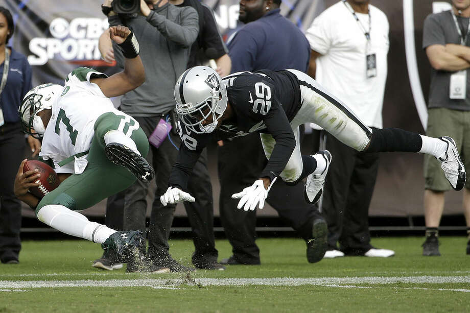 New York Jets quarterback Geno Smith (7) is hit by Oakland Raiders cornerback David Amerson (29) during the second half of an NFL football game in Oakland, Calif., Sunday, Nov. 1, 2015. The Raiders won 34-20. (AP Photo/Marcio Jose Sanchez)
