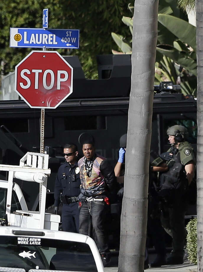 A suspect in a shooting, identified by police as Titus Colbert, is escorted away from an apartment building after an hours-long standoff with officials Wednesday, Nov. 4, 2015, in San Diego. Flights to the San Diego International Airport resumed after police took the gunman, who fired shots at a nearby apartment complex, posing a threat to air traffic, into custody. (AP Photo/Gregory Bull)