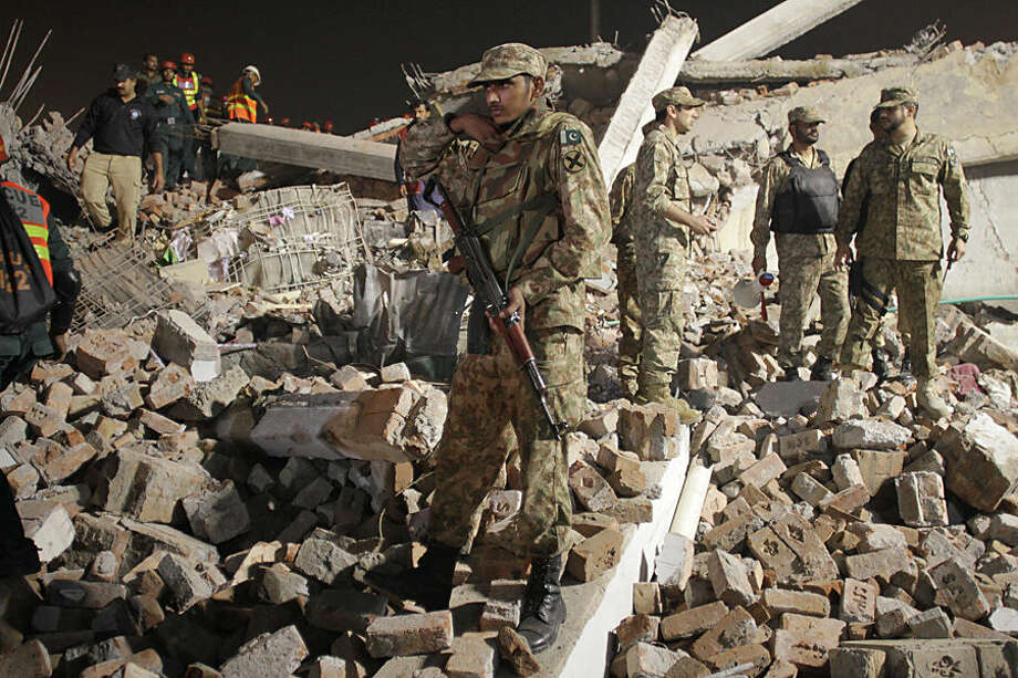 Pakistan army soldiers take part in rescue work following the collapse of a building in Lahore, Pakistan, Wednesday, Nov. 4, 2015. The factory building under construction in an industrial area on the outskirts of Pakistan's eastern city of Lahore collapsed on Wednesday, killing many workers and injuring dozens, officials said. (AP Photo/K.M. Chaudary)