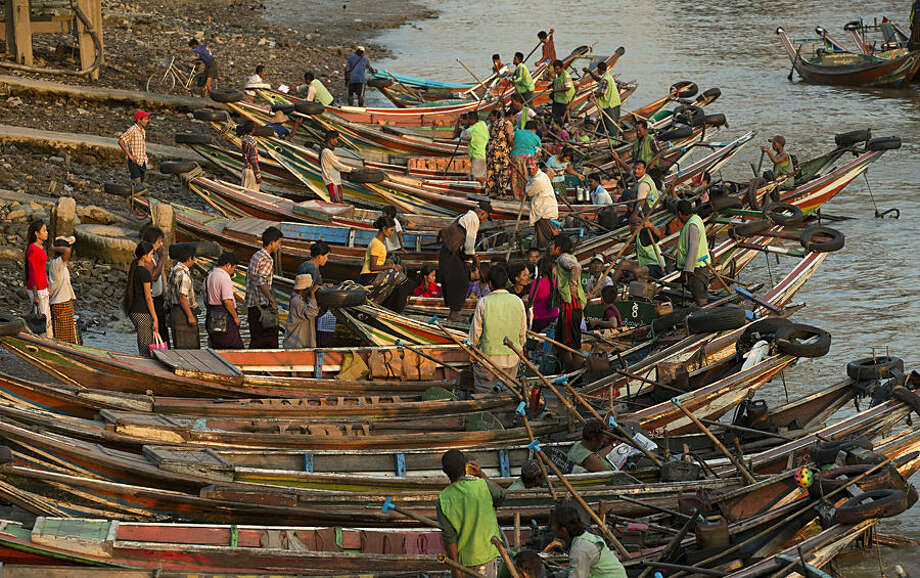Commuters prepare to board ferry boats across the Yangon river in Yangon, Myanmar, Wednesday, Nov. 4, 2015. On Sunday Myanmar will hold what is being viewed as the country's best chance for a free and credible election in a quarter of a century. (AP Photo/Mark Baker)