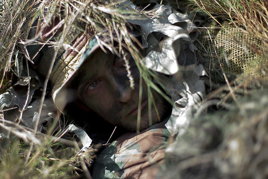 A Belgian soldier is camouflaged during a NATO military demonstration in Zaragoza, Spain, Wednesday Nov. 4, 2015. NATO is putting on its most fearsome display of military might in over a decade with soldiers, ships and planes meant to hone and test its abilities as well as send an unequivocal sign to Russia and other real or potential foes. For three weeks which started Oct. 21, more than 36,000 personnel from all 28 NATO allies and eight partner nations, 160 aircraft and 60 ships will be taking part in exercises across a wide swath of southern Europe from Portugal to Italy. (AP Photo/Abraham Caro Marin)