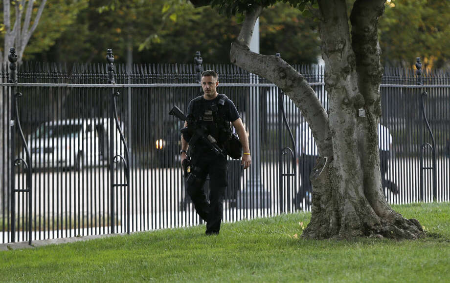 A member of security with a weapon walks along the interior of the perimeter fence on White House North Lawn along Pennsylvania Avenue in Washington, Monday, Sept. 22, 2014. The Secret Service tightened their guard outside the White House after Friday's embarrassing breach in the security of one of the most closely protected buildings in the world. A man is accused of scaling the White House perimeter fence, running across the lawn and entering the presidential mansion before agents stopped him. (AP Photo/Carolyn Kaster)