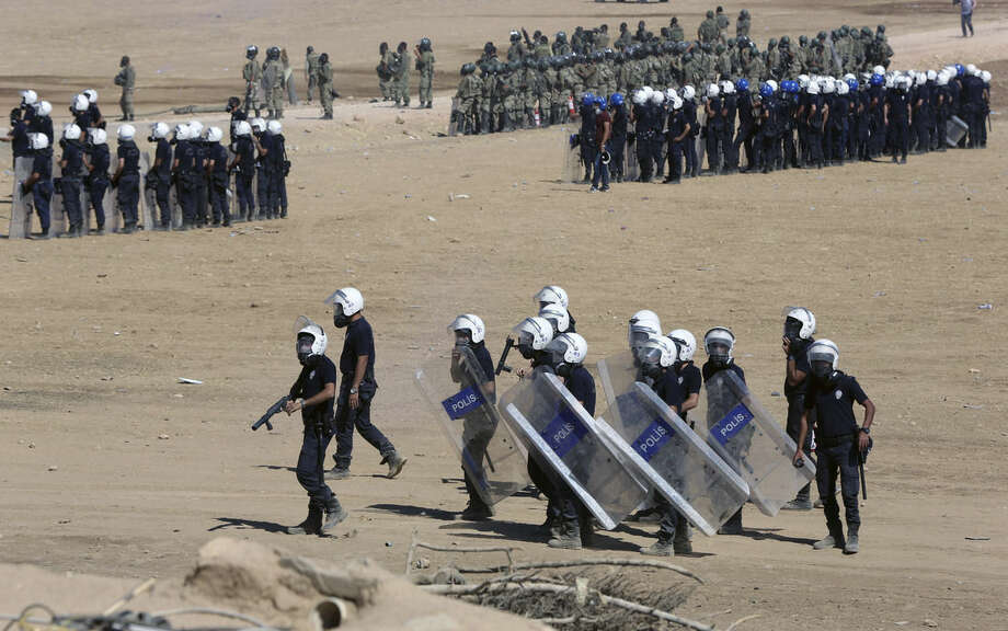 Riot police use teargas to disperse Kurdish demonstrators who were clashing with Turkish security forces as thousands of Syrian refugees continue to arrive at the border in Suruc, Turkey, Monday, Sept. 22, 2014. Turkey opened its border Saturday to allow in up to 60,000 people who massed on the Turkey-Syria border, fleeing the Islamic militants' advance on Kobani. (AP Photo/Burhan Ozbilici)
