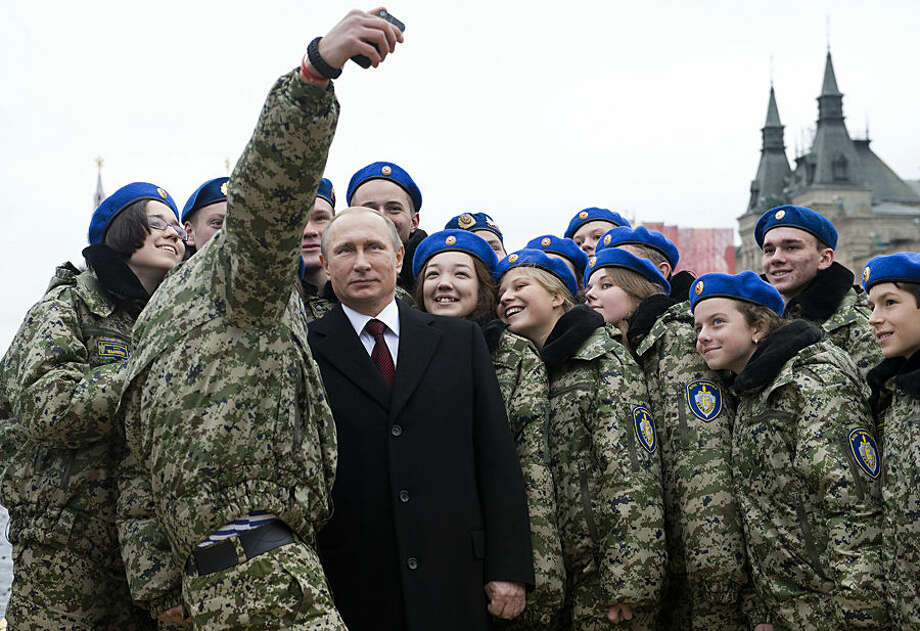 Russian President Vladimir Putin, center, poses for a photo with members of military patriotic club during a ceremony at the Red Square in Moscow on Wednesday, Nov. 4, 2015, during the National Unity Day, a national holiday which this year marks the 403rd anniversary of the 1612 expulsion of Polish occupiers from the Kremlin. (Natalia Kolesnikova/Pool Photo via AP)