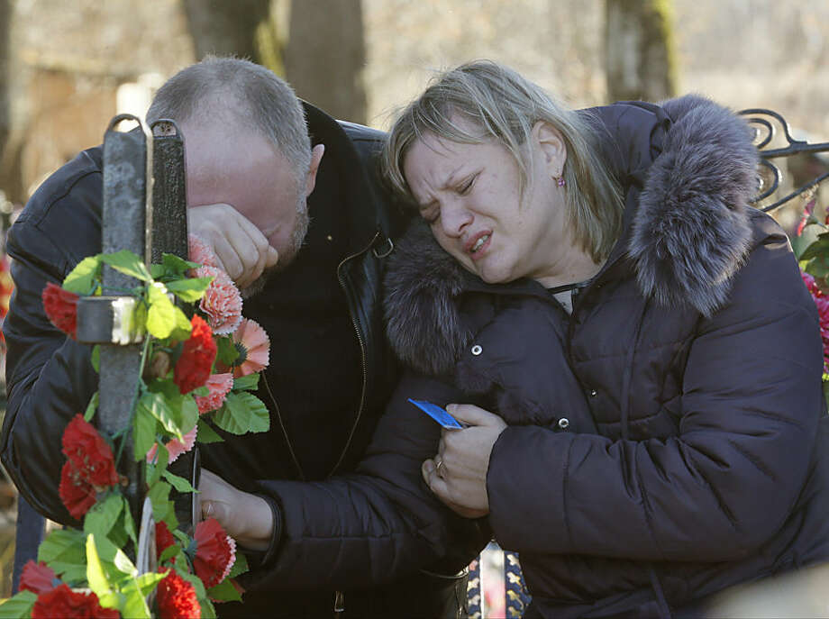 Nina Lushchenko's nephew Pavel and daughter Veronika react at her grave, after her funeral at a cemetery in the village of Sitnya, 80 km (about 50 miles) of Veliky Novgorod, Russia, Thursday, Nov. 5, 2015. The first victim of Saturday's plane crash in Egypt was laid to rest on Thursday following a funeral service in a medieval church in the north Russian city of Veliky Novgorod. Russia's Airbus 321-200 broke up over the Sinai Peninsula en route from the resort town of Sharm el-Sheikh to St. Petersburg, killing all 224 on board. (AP Photo/Dmitry Lovetsky)