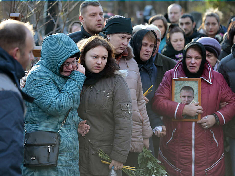 Maria, right, the mother of Alexei Alekseyev,, one of the plane crash victims, and his wife Lyudmila, second left, surrounded by relatives and friends, attend his funeral at Bogoslovskoye cemetery in St. Petersburg, Russia, Thursday, Nov. 5, 2015. The first victims of Saturday's plane crash over Egypt were laid to rest on Thursday following funeral services in St. Petersburg and Veliky Novgorod, Russia. Russia's Airbus 321-200 broke up over the Sinai Peninsula en route from the resort town of Sharm el-Sheikh to St. Petersburg, killing all 224 on board. (AP Photo/Ivan Sekretarev)