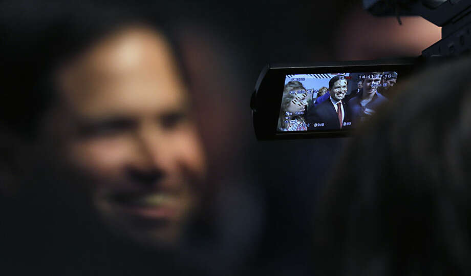 Republican presidential candidate Sen. Marco Rubio, R-Fla. is seen through a cameraman's viewfinder, smiles while greeting students during a campaign event at Saint Anselm College in Manchester, N.H., Wednesday, Nov. 4, 2015. (AP Photo/Charles Krupa)