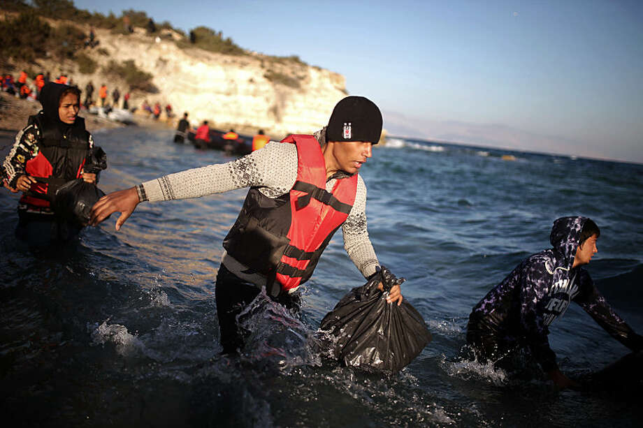 Migrants rush to catch a dinghy travelling to the Greek island of Chios, background, from the Turkish coast near Cesme, Izmir, Turkey, Wednesday, Nov. 4, 2015. More than 300,000 people have traveled on dinghies and boats from nearby Turkey to Greek islands this year, with dozens dying along the way. (AP Photo/Emre Tazegul)