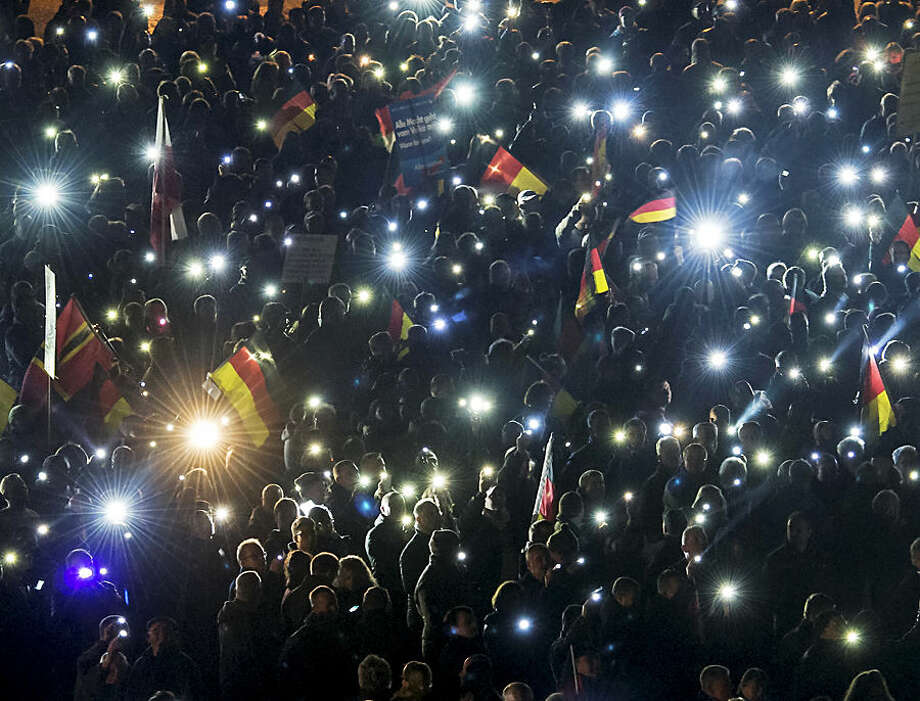 Thousands of people hold up the glowing displays of their mobile phones during a demonstration initiated by the Alternative for Germany (AfD) party against what they call the uncontrolled immigration and asylum abuse in Erfurt, central Germany, Wednesday, Nov. 4, 2015. (AP Photo/Jens Meyer)