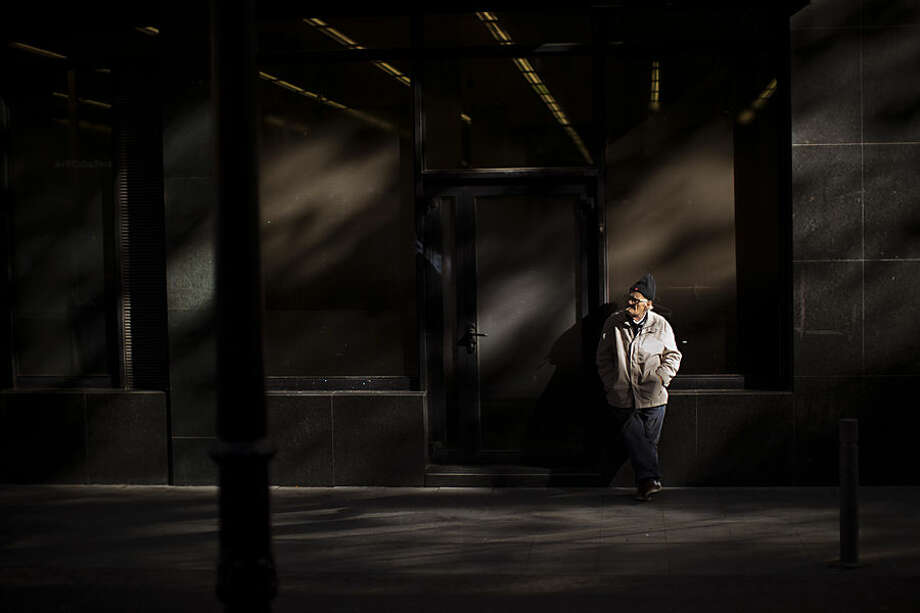 A man smokes outside a bank in Barcelona, Spain, Wednesday, Nov. 4, 2015. (AP Photo/Emilio Morenatti)