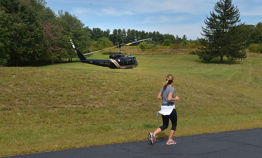 Hour Photo/Alex von Kleydorff A jogger runs past the town of Stratford's Police Rescue helicopter Eagle One after it lands at Dolce Center in Norwalk