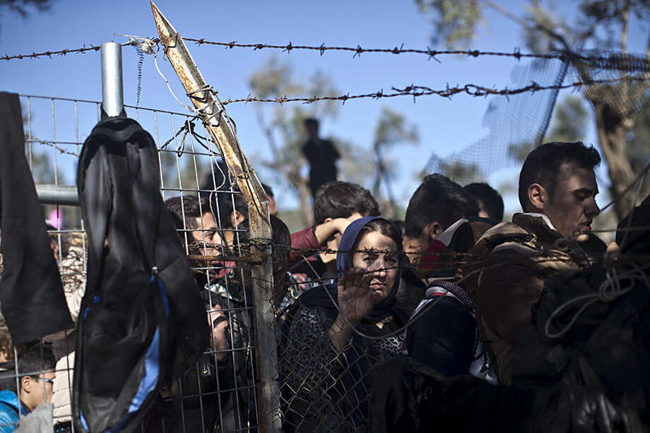 People wait in line to enter the migrant and refugee registration camp in Moria, on the island of Lesbos, Greece, Wednesday, Nov. 4, 2015. Dozens of overcrowded inflatable dinghies and wooden boats reach Greek islands daily, even during bad weather, and hundreds have drowned as their overloaded and unseaworthy boats overturned or sank. (AP Photo/Marko Drobnjakovic)
