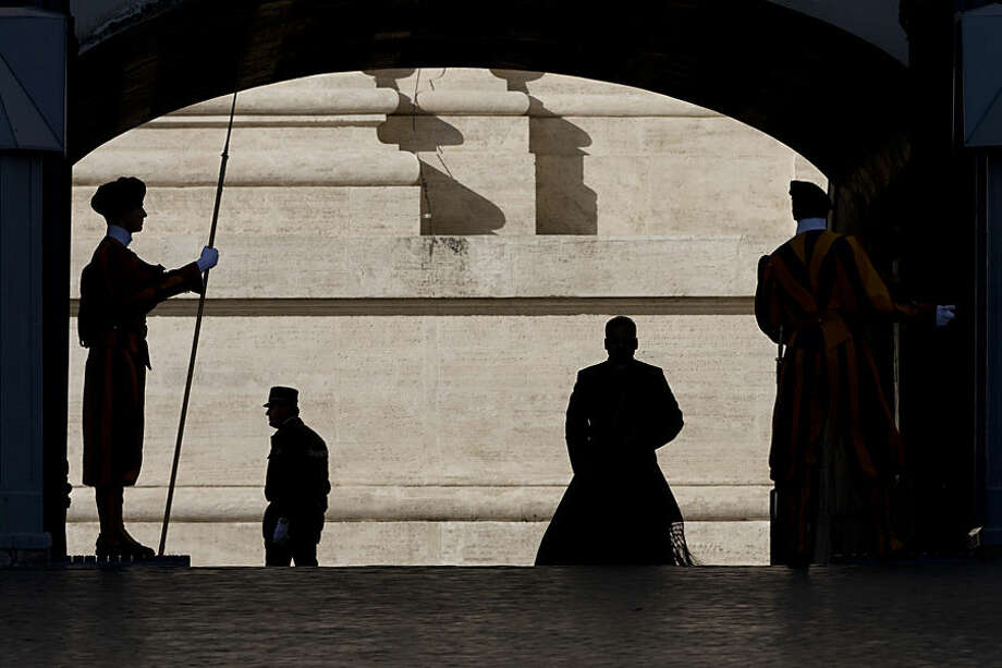 From left, a Swiss Guard, a Vatican Gendarmerie guard and a priest are silhouetted before Pope Francis' arrival for his weekly general audience in St. Peter's Square at the Vatican, Wednesday, Nov. 4, 2015. (AP Photo/Alessandra Tarantino)