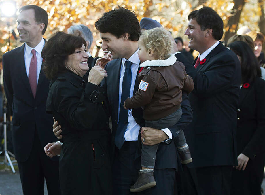 Prime Minister-designate Justin Trudeau holds his son Hadrien while hugging his mother Margaret outside Rideau Hall in Ottawa on Wednesday, Nov. 4, 2015. Trudeau has been sworn in as Canada's next prime minister, following in the footsteps of his storied father. (Sean Kilpatrick/The Canadian Press via AP) MANDATORY CREDIT