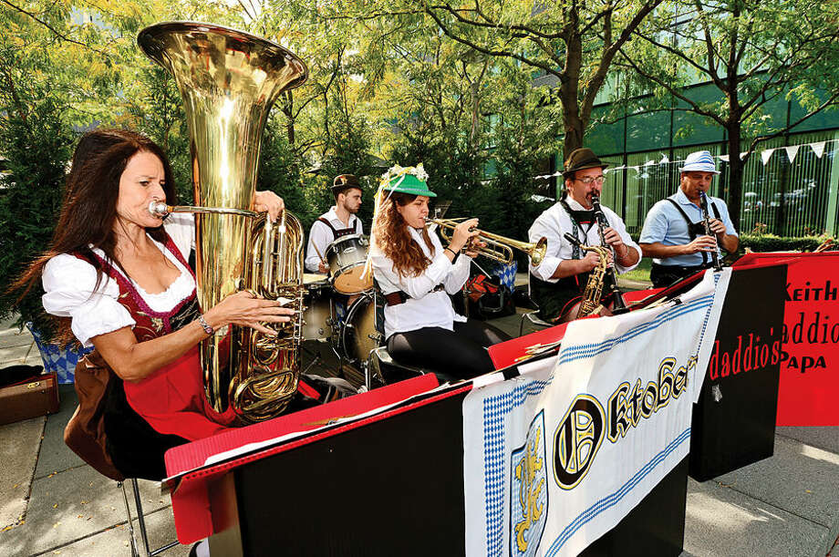 Hour photo / Erik Trautmann Leslie Havens, left, plays with Daddario's Oompah Band during Building and Land Technology's Towers Tenant Appreciation Oktoberfest Picnic Wednesday.
