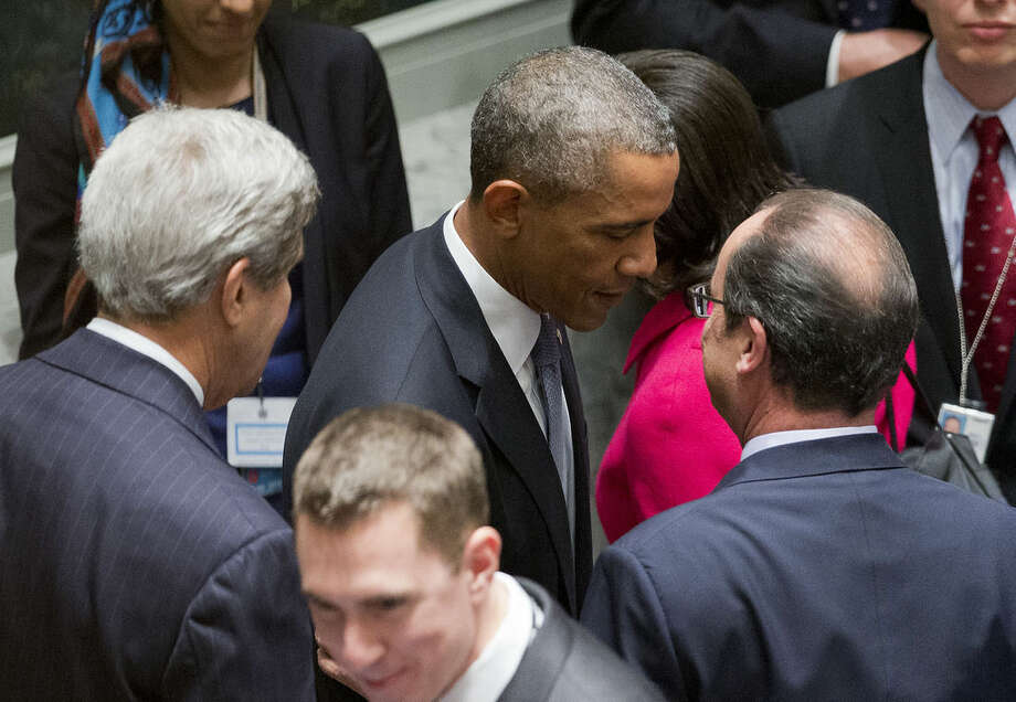President Barack Obama, accompanied by Secretary of State John Kerry, talks with French President Francois Hollande, before the start of the UN Security Council summit on foreign terrorist, Wednesday, Sept. 24, 2014, at the UN headquarters. (AP Photo/Pablo Martinez Monsivais)