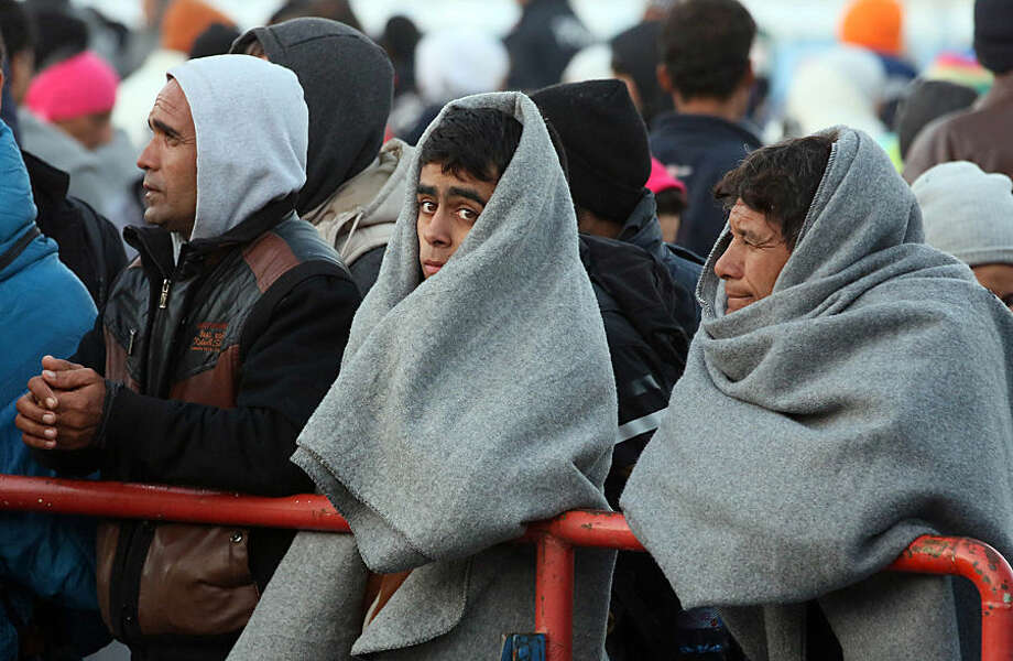 Migrants wait for buses after crossing the border between Slovenian and Austria in Spielfeld, Austria, Tuesday, Nov. 3, 2015. Tens of thousands of people are trying to reach central and northern Europe via the Balkans but often have to wait for days in mud and rain at the Serbian, Croatian and Slovenian borders. (AP Photo/Ronald Zak)