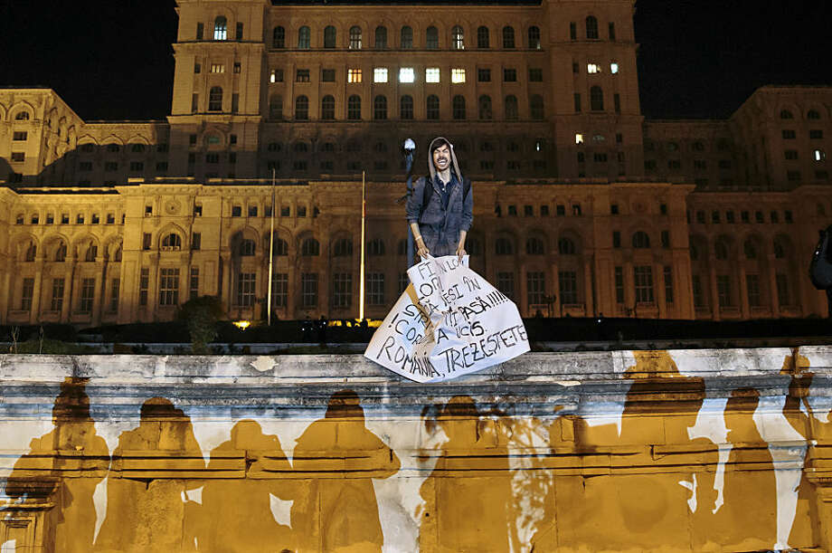 "A protester screams holding a paper that reads ""Corruption has killed - Romania wake up"" back-dropped by the communist era built House of the People, now housing the Romanian parliament during a rally joined by thirty-five thousand people, according to local media quoting the Romanian Gendarmerie, calling for early elections, in Bucharest, Romania, Wednesday, Nov. 4, 2015. Prime Minister Victor Ponta announced the resignation of his government Wednesday following huge protests the day before in the wake of a nightclub fire that killed more than 30 people.(AP Photo/Vadim Ghirda)"