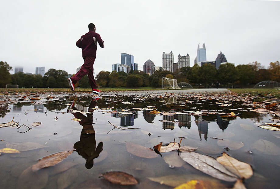 Fallen leaves lie in a puddle as a jogger passes the midtown skyline in Piedmont Park, Wednesday, Nov. 4, 2015, in Atlanta. The foggy, rainy weather over the area for the past several days will remain through Thursday with mild temperatures continuing through the end of the week. (AP Photo/David Goldman)