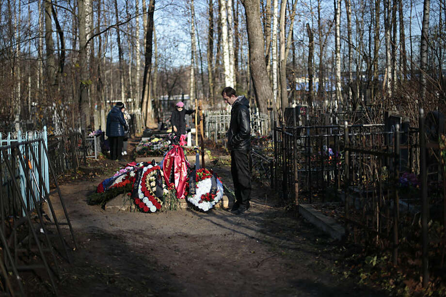 A realativ of Alexei Alekseyev, one of the plane crash victims, stands at his grave after the funeral at Bogoslovskoye cemetery in St. Petersburg, Russia, Thursday, Nov. 5, 2015. The first victims of Saturday's plane crash over Egypt were laid to rest on Thursday following funeral services in St. Petersburg and Veliky Novgorod, Russia. Russia's Airbus 321-200 broke up over the Sinai Peninsula en route from the resort town of Sharm el-Sheikh to St. Petersburg, killing all 224 on board. (AP Photo/Ivan Sekretarev)