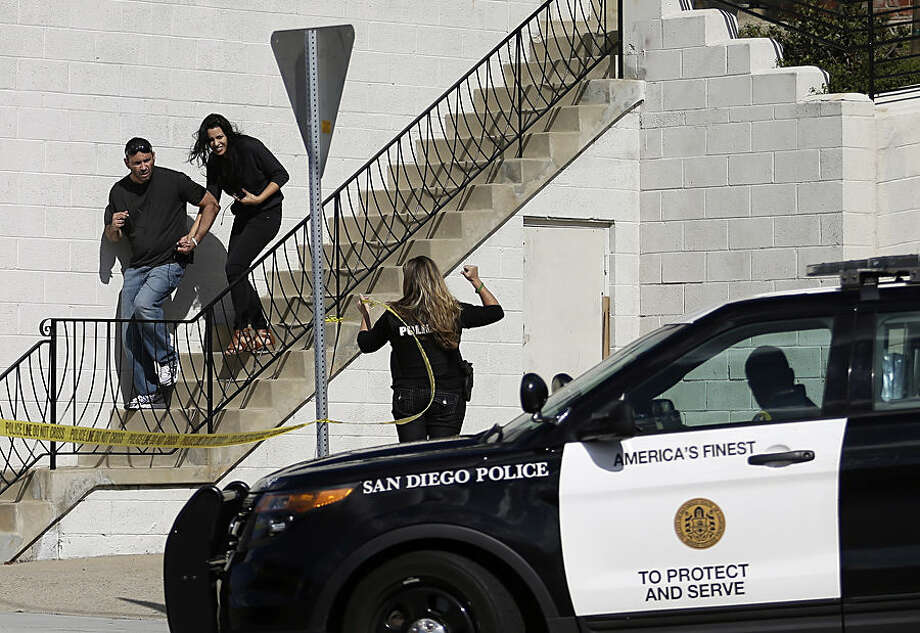 San Diego police officers assist a couple as they evacuate a building in San Diego on Wednesday, Nov. 4, 2015. A man with a high-powered gun was firing sporadically inside a San Diego apartment complex, causing the city's nearby airport to stop planes from landing, authorities said. (AP Photo/Gregory Bull)
