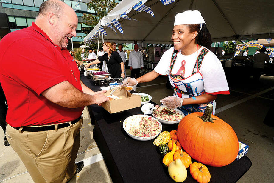Hour photo / Erik Trautmann FLIK food service worker Brenda Mack serves up german potato salad to John Fritz during Building and Land Technology's Towers Tenant Appreciation Oktoberfest Picnic Wednesday.