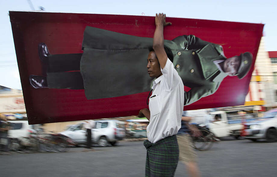 A supporter of Myanmar opposition leader Aung San Suu Kyi's National League for Democracy party carries a large photo of her father, independence hero General Aung San to a campaign rally to conclude their election campaign in Yangon, Myanmar, Thursday, Nov. 5, 2015. On Sunday Myanmar will hold what is being viewed as the country's best chance for a free and credible election in a quarter of a century. (AP Photo/Mark Baker)