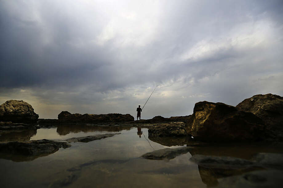 A Lebanese angler casts his fishing pole from a rocky coastal area along the Beirut coastline under cloudy skies, Lebanon, Wednesday, Nov. 4, 2015. A thick sandstorm cloaked the Middle East on Wednesday, clouding skies across the region. (AP Photo/Hassan Ammar)