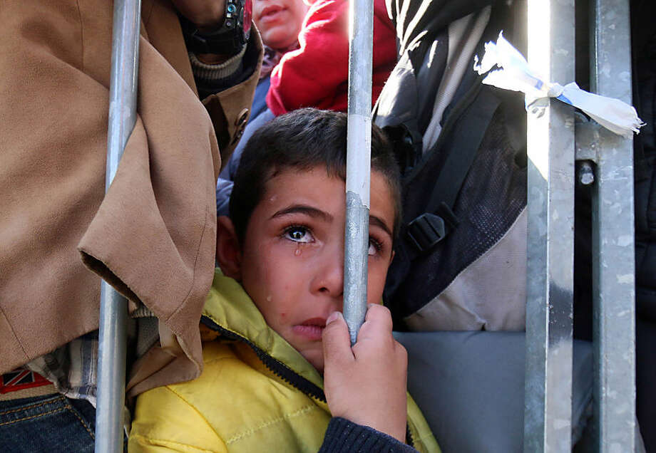 A migrant boy waits to cross the border between Slovenia and Austria in Sentilj, Slovenia, Wednesday, Nov. 4, 2015. Hundreds of thousands of migrants have flooded to northern Europe in recent months seeking to escape war and poverty and start a new life. (AP Photo/Ronald Zak)