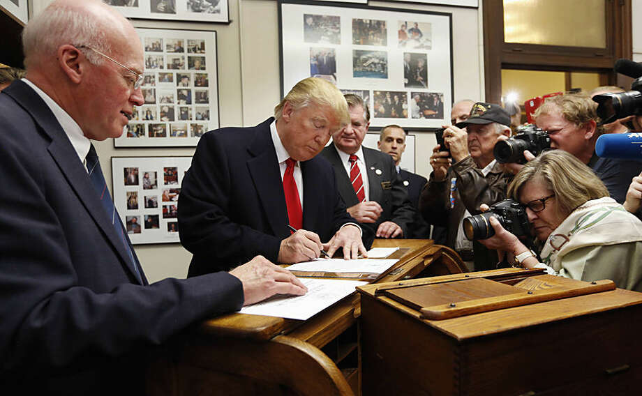 New Hampshire Secretary of State Bill Gardner watches at left as Republican presidential candidate Donald Trump fills out his papers to be on the nation's earliest presidential primary ballot, Wednesday, Nov. 4, 2015, at The Secretary of State's office in Concord, N.H. (AP Photo/Jim Cole)