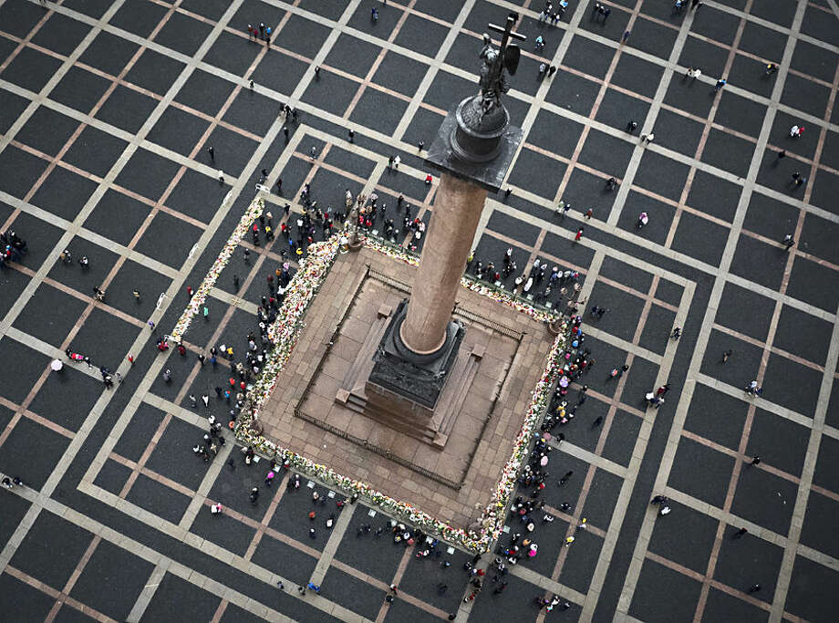 People gather to place floral tributes at the foot of the Alexander Column at Dvortsovaya (Palace) Square in St. Petersburg, Russia, Wednesday, Nov. 4, 2015. A Russian official says families have identified the bodies of 33 victims killed in Saturday's plane crash over Egypt. The Russian jet crashed over the Sinai Peninsula early Saturday, killing all 224 people on board. Most of them were holidaymakers from Russia's St. Petersburg. (AP Photo/Dmitry Lovetsky)