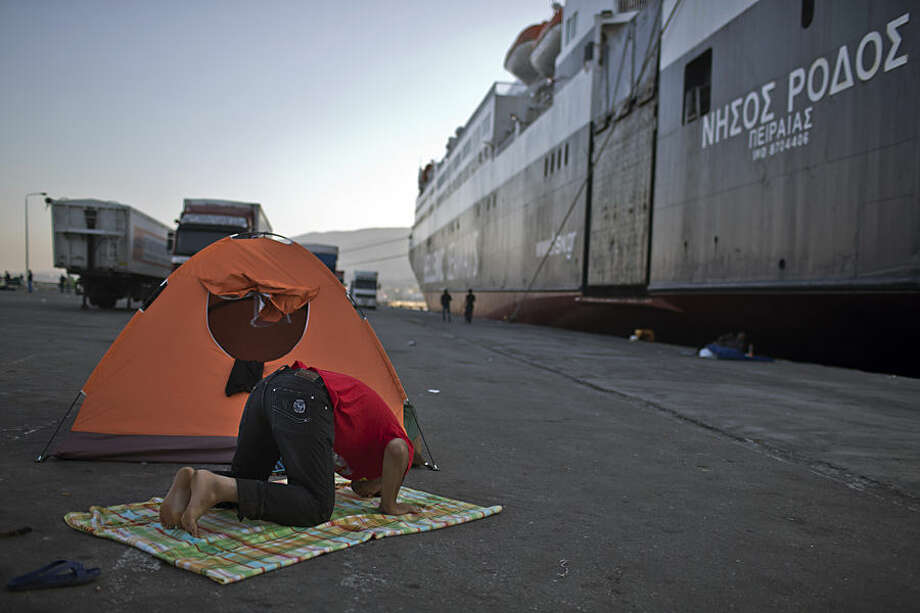 A man prays next to a ferry boat in the port of Mytilene, on the island of Lesbos, Greece, Thursday, Nov. 5, 2015. Greek ferries, which were on strike and have trapped thousands of refugees on eastern Aegean islands, will start operating again on Friday. (AP Photo/Marko Drobnjakovic)